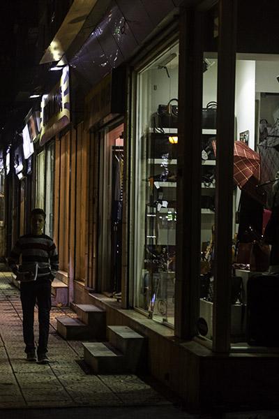 09 Boy walking past shops in Tirana, Albania, in 2014