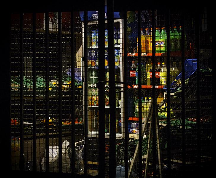 37 Detail through grate of locked shop in Tirana, Albania, 2014