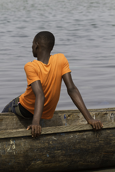 Man leaning on canoe, West Point settlement --Monrovia, Liberia