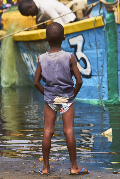 Boy watching fishing boat unload, West Point settlement --Monrovia, Liberia