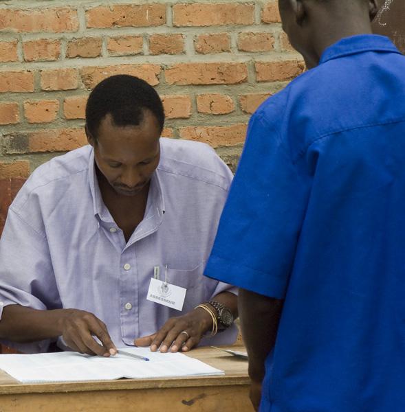 16 Man checking voter against registration list in Buturere, Bujumbura Rural Commune, Burundi, in 2005