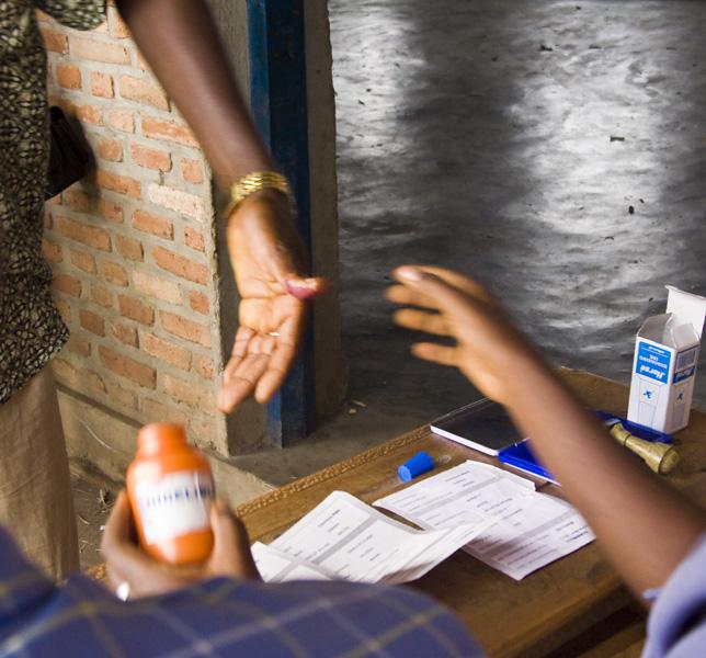 21 Representative dipping voter's finger in indelible ink  in Buterere, Bujumbura Rural Commune, Burundi, in 2005