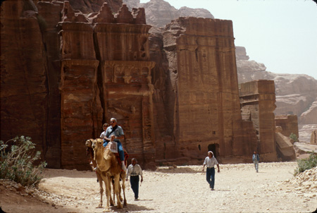 Tourists enjoying camel ride through Outer Siq Petra, Jordan