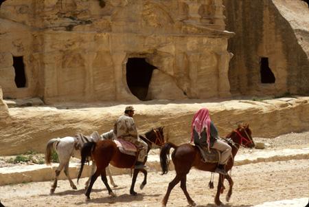 Riders passing the Bab as-Siq Triclinium Petra, Jordan