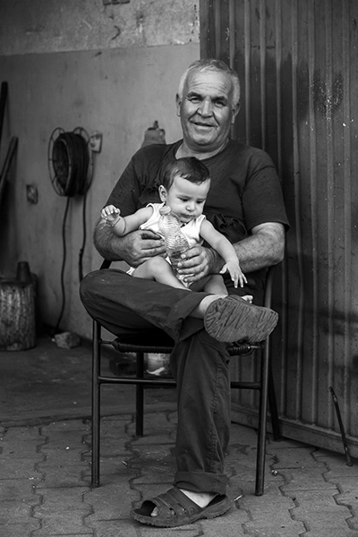 044 Mechanic with grandchild in Tophane neighborhood, Prishtina, Kosovo